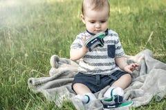 Un bebé lindo que se sienta y que juega con su zapato en naturaleza en un parque del verano en hierba fotografía de archivo libre de regalías