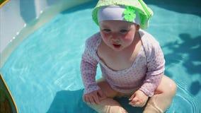 Un bebé pequeño y divertido que está en la piscina cubre su cara con sus manos almacen de metraje de vídeo