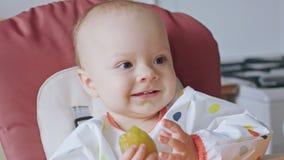 Un bebé que come el ciruelo en casa Foto de archivo libre de regalías
