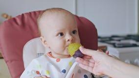 Un bebé que come el ciruelo en casa Imagenes de archivo