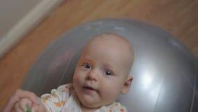 Un bebé que miente en una bola gimnástica de plata grande almacen de video