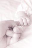 Un bebé que sostiene el dedo índice del padre Imagen de archivo libre de regalías