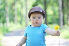 Un bebé que sostiene una flor Imagen de archivo