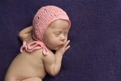 Un bebé recién nacido duerme en una tela escocesa de la lila fotografía de archivo libre de regalías