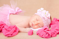 Un bebé recién nacido durmiente que lleva una venda y un tutú rosados Imágenes de archivo libres de regalías