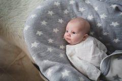 Un bebé recién nacido está mintiendo en una colcha gris y está mirando alguien imagen de archivo libre de regalías