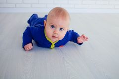 Un bebé recién nacido está poniendo en un piso laminado fotos de archivo