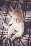 Un bebé rubio lindo con los ojos azules en ropa ligera se sienta en una colcha de la tela escocesa en la cama y mira para arriba fotos de archivo libres de regalías