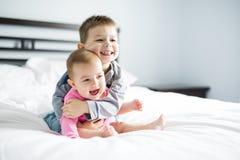 Un bebé y su hermano en la cama que se divierte foto de archivo