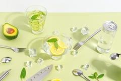 Un becher di vetro, una bottiglia dell'acqua del cetriolo, frutti e coltelleria su un fondo verde chiaro Concetto creativo di Min fotografie stock libere da diritti