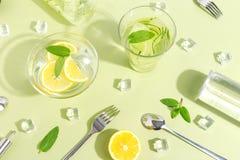 Un becher di vetro, una bottiglia dell'acqua del cetriolo, frutti e coltelleria su un fondo verde chiaro Concetto creativo di Min immagini stock