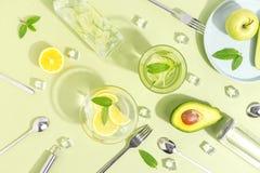 Un becher di vetro, una bottiglia dell'acqua del cetriolo, frutti e coltelleria su un fondo verde chiaro Concetto creativo di Min immagini stock libere da diritti