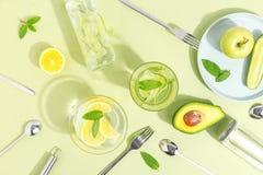 Un becher di vetro, una bottiglia dell'acqua del cetriolo, frutti e coltelleria su un fondo verde chiaro Concetto creativo di Min fotografia stock libera da diritti