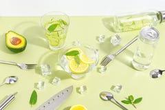 Un becher di vetro, una bottiglia dell'acqua del cetriolo, frutti e coltelleria su un fondo verde chiaro Concetto creativo di Min immagine stock