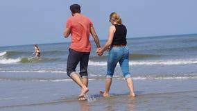 Un'bei uomo e donna delle coppie in jeans mette la camminata in cortocircuito sul tenersi per mano tropicale della spiaggia Vanno archivi video
