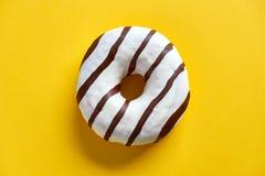 Un beignet avec le glaçage blanc de glace et les rayures du chocolat photographie stock