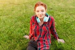 Un bel étudiant roux avec des taches de rousseur est habillé dans une chemise à carreaux rouge avec des écouteurs se reposant sur photographie stock libre de droits