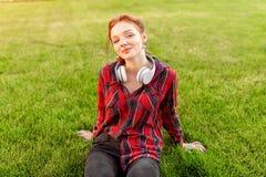 Un bel étudiant roux avec des taches de rousseur est habillé dans une chemise à carreaux rouge photos libres de droits