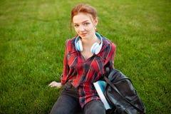 Un bel étudiant roux avec des taches de rousseur est habillé dans une chemise à carreaux rouge images stock