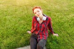 Un bel étudiant roux avec des taches de rousseur est habillé dans une chemise à carreaux rouge photo stock