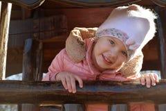 Un bel enfant blond heureux caucasien de fille riant et regardant hors de la fenêtre de sa maison en bois dans le jardin dehors image stock