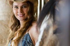 Un bel extérieur hispanique de cheval de Poses With A de modèle de brune dans un environnement familial photo stock