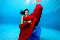 Un bello adolescente con un panno rosso e blu in sue mani che posano underwater e che esaminano la macchina fotografica Immagine Stock Libera da Diritti