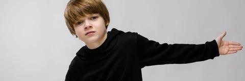 Un bello adolescente in maglione nero e jeans della luce Il ragazzo ha spanto le sue mani in entrambe le direzioni immagine stock