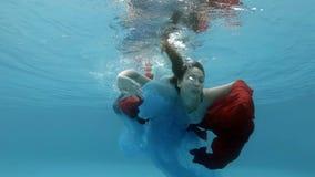 Un bello adolescente in un vestito nuota underwater in una piscina, giochi con un panno rosso e blu vicino alla superficie video d archivio