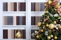 Un bello albero di Natale decorato sui precedenti di uno scaffale per libri con molti libri dei colori differenti e dell'orologio Fotografia Stock