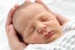 Un bello bambino addormentato in mani Fotografia Stock Libera da Diritti