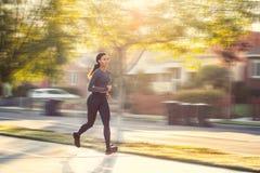 Un bello funzionamento sportivo della donna su un marciapiede in un hous privato Fotografia Stock