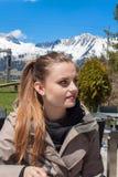 Un bello giovane castana sul terrazzo di un hotel della montagna Bella ragazza che riposa sul terrazzo Ragazza con capelli marron Fotografie Stock Libere da Diritti