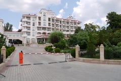 Un bello hotel multipiano con i balconi con un'area verde pittoresca accanto contro un cielo blu con le nuvole immagini stock libere da diritti