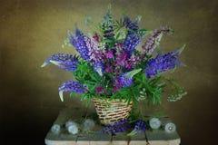 Un bello mazzo dei fiori in un canestro immagine stock