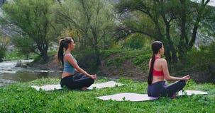 In un bello posto alla natura con le signore del fiume e della montagna che praticano l'yoga sulla stuoia abbia meditazione li po archivi video