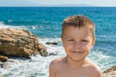 Un bello ragazzino che posa su una spiaggia dal mare fotografie stock libere da diritti