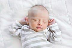 Un bello ragazzo di neonato addormentato su una coperta bianca È Fotografie Stock