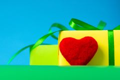 Un bello regalo di verde giallo e un cuore amoroso per un compleanno Fotografia Stock