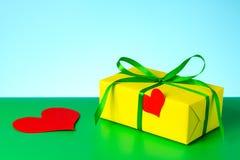 Un bello regalo giallo e un cuore amoroso per un compleanno Fotografia Stock Libera da Diritti