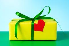 Un bello regalo giallo e un cuore amoroso per un compleanno Fotografia Stock