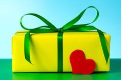 Un bello regalo giallo e un cuore amoroso per un compleanno Fotografie Stock Libere da Diritti