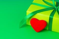 Un bello regalo verde e un cuore rosso amoroso per un compleanno Fotografia Stock
