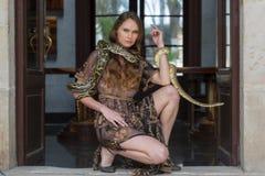 Un bello serpente castana ispano del boa constrictor di Poses With A del modello intorno al suo corpo fotografie stock libere da diritti