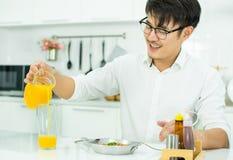 Un bello sta versando il succo d'arancia al vetro fotografia stock libera da diritti