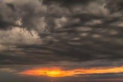 Un bello tramonto firelike con le nuvole scure tempestose drammatiche Fotografie Stock