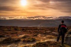 Un bello tramonto in montagne con un viaggiatore con zaino e sacco a pelo maschio ingiungere una vista splendida immagini stock