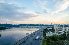 Un bello tramonto sopra la città Paesaggio industriale con il fiume della città e la vista del centro di Kiev della città fotografia stock libera da diritti