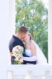 Un beso de los pares nuevamente casados en las columnas fotografía de archivo