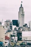 Un bianco alto ha invecchiato la torre con una bandiera sugli aumenti superiori nella metropoli Immagine Stock Libera da Diritti
